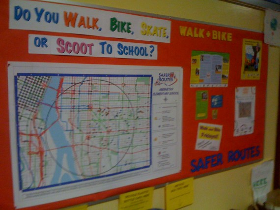 in the hallway of the school is this big board with info about walk and bike